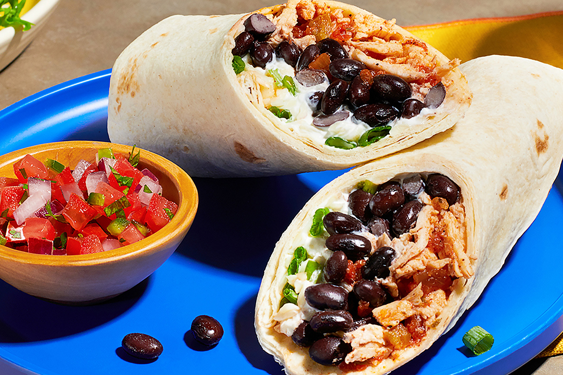 A chicken and black bean burrito sliced in half on a blue plate with small bowl of tomato salsa