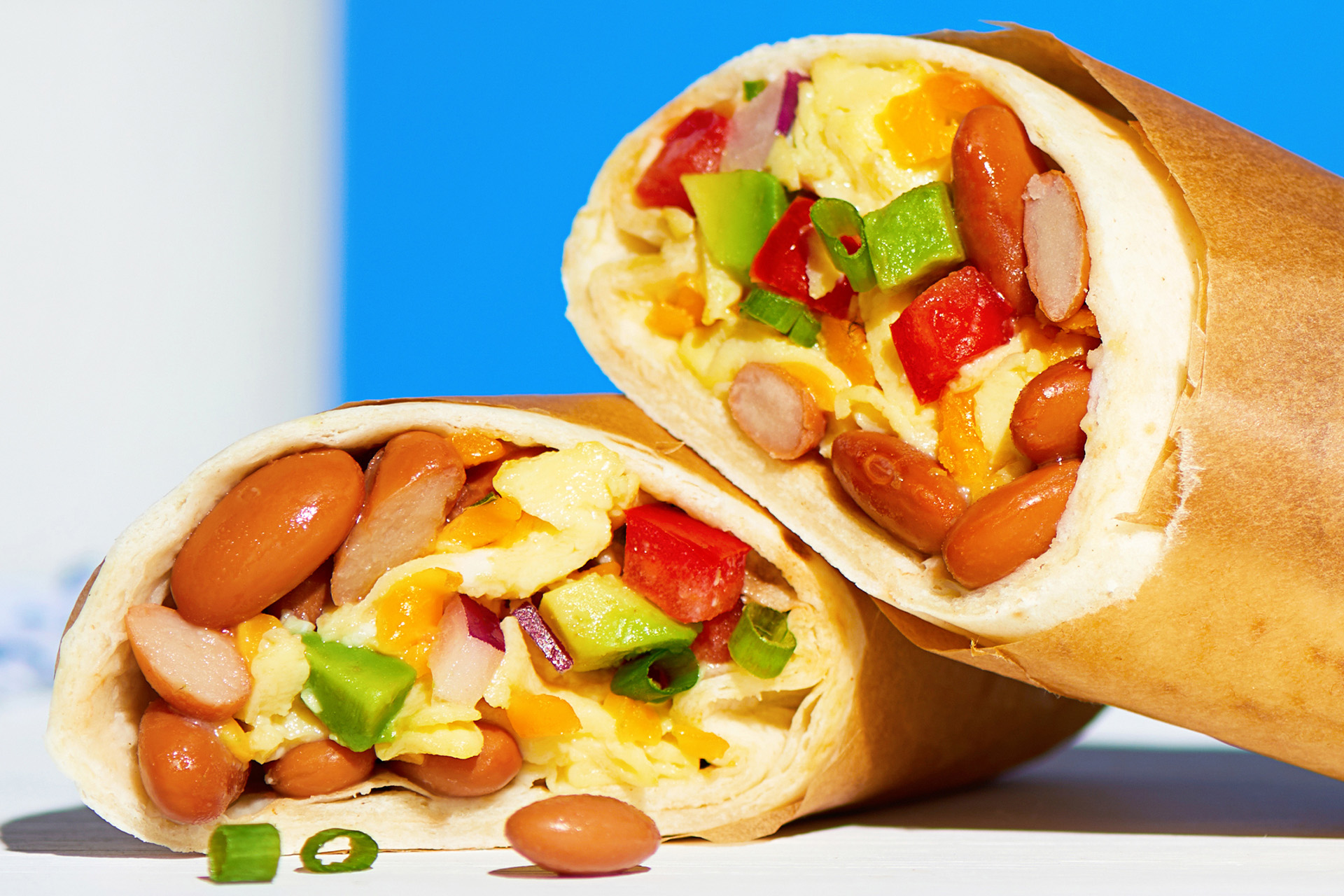 A close up of a breakfast burrito with beans, eggs, and cheese cut in half