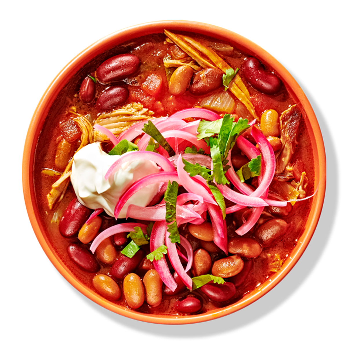 Chicken and bean chili in yellow bowl garnished with sour cream and onion